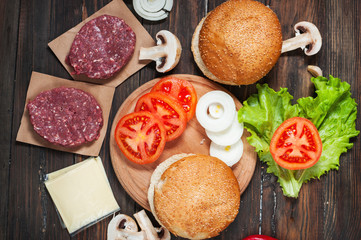 Homemade hamburger ingredients. Raw minced beef, fresh bun, slice of cheese, tomato, onion rings, lettuce on wood background
