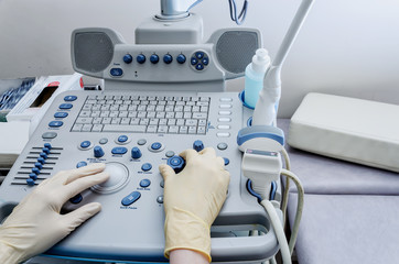 The doctor's hands on the ultrasound machine