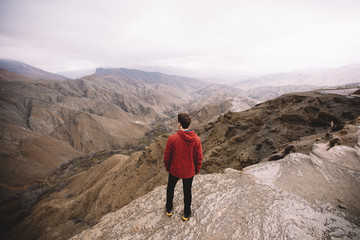 Male standing in mountains looking into distance