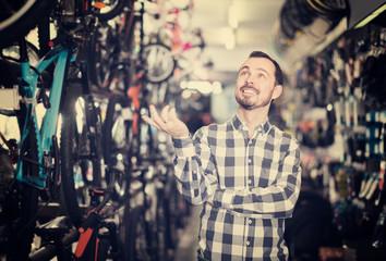 joyous man in bicycle shop chooses for himself sports bike
