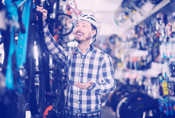 friendly man in helmet chooses for himself sports bike in bicycle shop