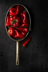 Still life of saucepan containing red bell peppers, single chilli beside pan, overhead view