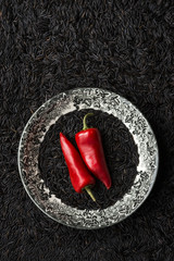 Still life of two red chillies on plate of black rice, with background of balck rice, overhead view