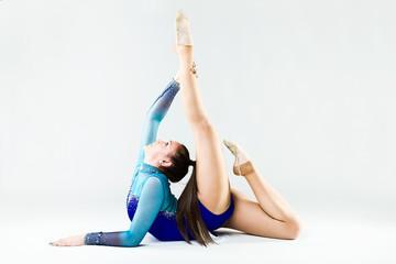 Beautiful gymnast athlete doing exercise. Isolated on white.