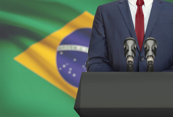 Businessman or politician making speech from behind a pulpit with national flag on background - Brazil