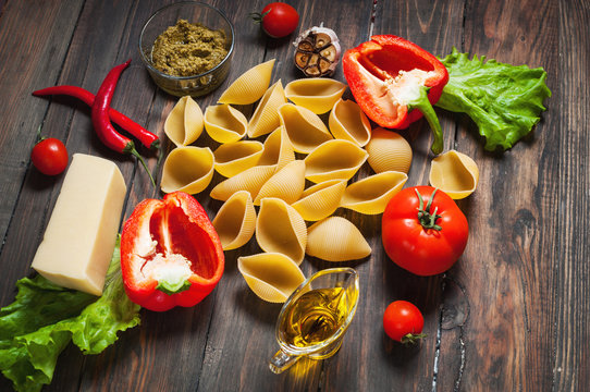 Ingredients for cooking pasta. Conchiglioni, cherry-tomatoes, cheese, oil, garlic, pepper on rustic wood