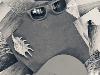 Sunglasses, shell, cap, and pictures with the image of the sea on a wooden surface