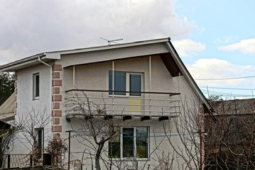 Частное,серое здание с балконом на фоне неба