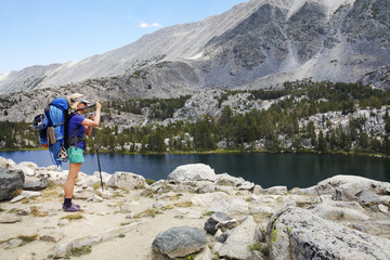 Female hiker with backpack standing by lake