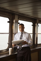 Man reading newspaper and having coffee on ferry