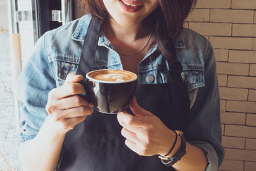 barista woman holding cup of tasty latte with tulip art ,vintage effect