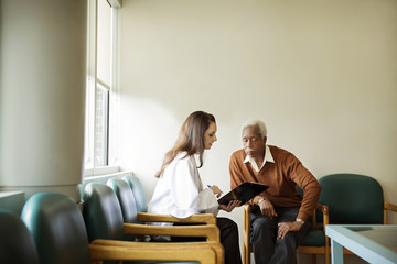 Doctor talking with patient in waiting room