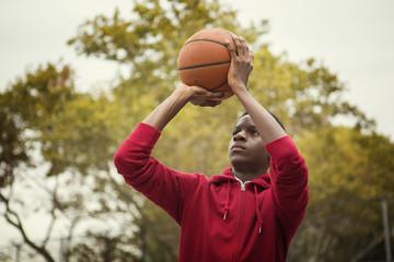 Teenage boy (14-15) playing basketball