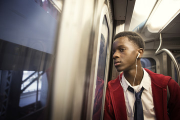 Teenage boy (14-15) listening to music in train