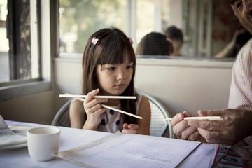 Grandfather teaching granddaughter to use chopsticks