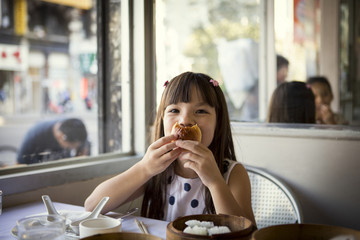Girl (6-7) having lunch in restaurant