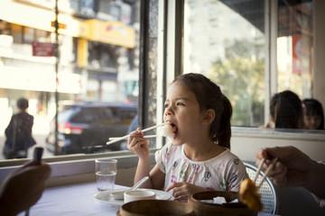 Girl (8-9) having lunch in restaurant
