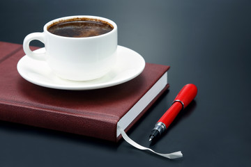 the red pen is a saucer Cup of black coffee
