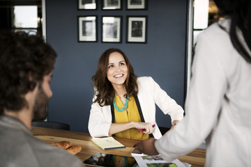 People interacting in office images on wall in background