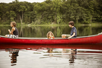 Boys (12-13, 8-9) and girl (4-5) in red boat forest in background