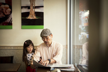 Grandfather and granddaughter (6-7) reading newspaper in cafe