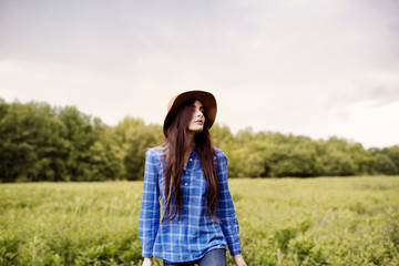Portrait of young woman standing in meadow