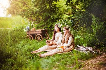Beautiful little girls in a white dress posing in the grass. Sunset light.