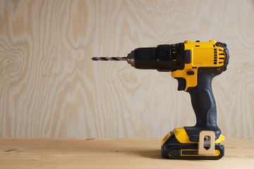 cordless drill against wooden background, rechargeable drill, modern electric tool for tradesmen