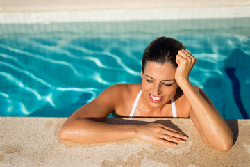 Joyful woman relaxing and enjoying summer vacation in hotel resort spa swimming pool.