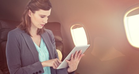 Composite image of businesswoman working on digital tablet