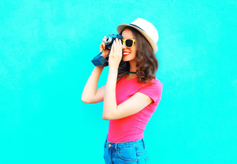 Fashion pretty woman taking picture wearing straw summer hat, sunglasses and vintage camera over colorful blue background