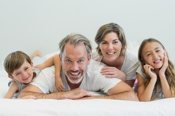 Portrait of smiling family lying on bed in bedroom