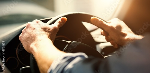 Cropped hands of man holding steering wheel