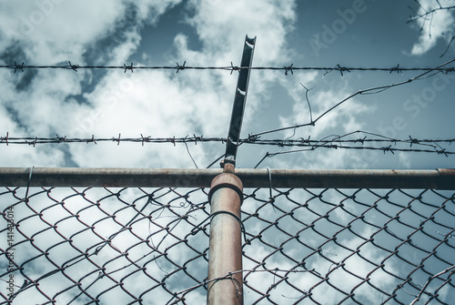 Abstract chain link fence with barbed wire. Broken chain steel fence ...