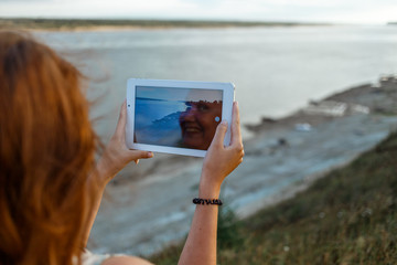Back view of a young woman wanderer is making photo with portable tablet camera during her vacations in village meadows with great river. In reflection of the screen the smiling face of the girl is