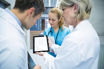 Medical team discussing over digital tablet