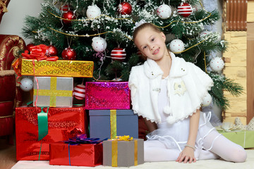 Little girl with gifts by the Christmas Tree