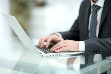 Businessman working at office with hand on keyboard. Close up
