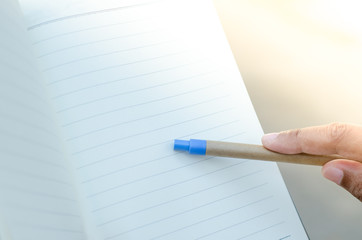 Finger with pen pointing to notebook on nature light background