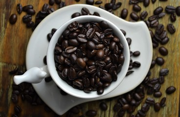 Coffee beans in white coffee cup with coffee beans scattered in background
