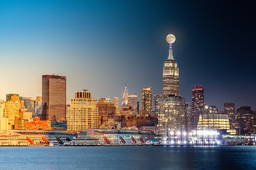 Fotomurales - Composite day to night timelapse with the full moon rising above New York City skyline.