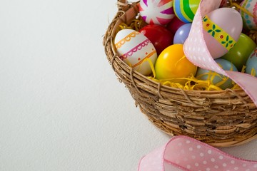 Various Easter eggs with ribbon in wicker basket