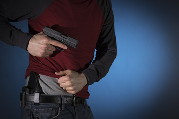 Man drawing a concealed carry pistol from a holster