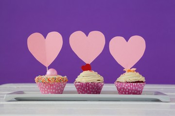 Wall Mural - Close-up of three cupcakes with heart cards