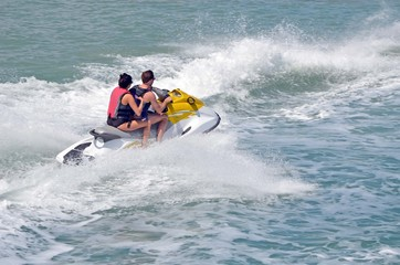 Young man and woman riding tandem on a  speeding jet ski.