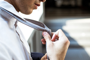 Businessman  adjusting tie closeup