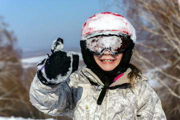 Girl skier, in red helmet and glasses shows thumb up