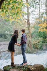 pair of beautiful brunette with a guy holding hands in nature at the waterfall fall trees