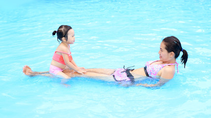 Pretty little girl with her mother playing in swimming pool outdoors