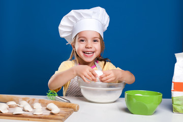 The little girl is cooking and preparing food on blue background